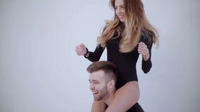 Het jonge blije paar heeft pret het dansen Geekpaar het dwaze dansen Paar die in pyjama's dansen Het sexy vrouw dansen stock videobeelden