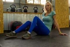 Het jonge blonde in groene T-shirt en tennisschoenen en blauwe leggins zit royalty-vrije stock foto's