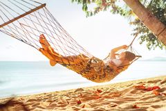 Het jonge blonde longhaired vrouw ontspannen in hangmat scharnierend tussen palmen op het zandstrand royalty-vrije stock afbeeldingen