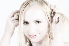 Het jonge blonde meisje spelen met haar haar Stock Foto's