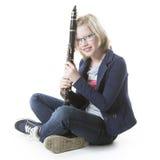 Het jonge blonde meisje zit en houdt klarinet in studio royalty-vrije stock foto