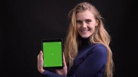 Het jonge blonde model werken met tablet toont het zijn groen scherm aan camera om app op zwarte achtergrond te adviseren stock video