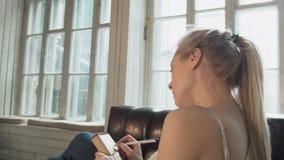 Het jonge blonde schrijft in een oud notitieboekje zijn geheugen zittend op een stoel voor een venster Een mooi tienermeisje stock videobeelden