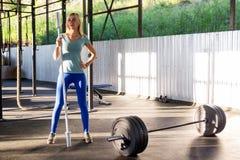 Het jonge blondemeisje in blauwe beenkappen en een groene T-shirt is standi stock fotografie