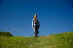 Het jonge blondemeisje loopt in openlucht, op gras behandeld gebied Stock Foto