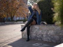 Het jonge blondemeisje met mooie lange benen in laarzen zit op de straat stock fotografie