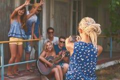 Het jonge blondemeisje met ontzetting neemt een foto van groepen haar vrienden met haar smartphone dichtbij de houten vakantiecab stock foto's