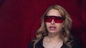 Het jonge blondemeisje zet op beschermende glazen die het UV witten krijgen Vóór de procedure van tanden het witten stock video