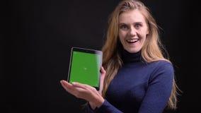 Het jonge blondemodel zet app op tablet aan en toont het zijn groen scherm vreugdevol aan camera op zwarte achtergrond stock video