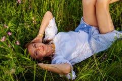 Het jonge blondevrouw liggen op groen gras, Vrijheid en ontspant concept, Vrijheid en ontspant concept stock fotografie