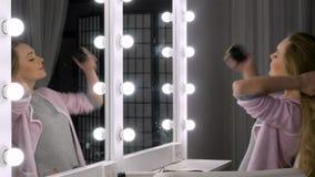 Het jonge blondevrouw stellen met mooi kapsel voor spiegel stock video
