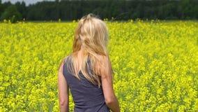 Het jonge blondevrouw stellen op mooi raapzaadgebied stock video