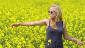 Het jonge blondevrouw stellen op mooi raapzaadgebied stock videobeelden