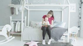 Het jonge boek van de mammalezing aan zuigelingsmeisje in kinderdagverblijf stock videobeelden