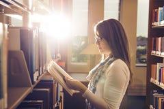 Het jonge boek van de meisjeslezing bij bibliotheek over mooie zonneschijn Stock Afbeeldingen
