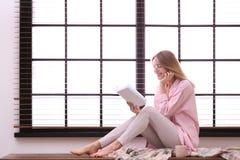 Het jonge boek van de vrouwenlezing dichtbij venster met zonneblinden thuis royalty-vrije stock afbeeldingen