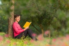 Het jonge boek van de vrouwenlezing in het park Royalty-vrije Stock Fotografie