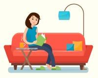 Het jonge boek van de vrouwenlezing op bank thuis Stock Afbeeldingen
