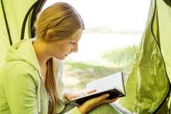 Het jonge boek van de vrouwenlezing in tent in het midden van het bos Stock Afbeeldingen
