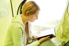 Het jonge boek van de vrouwenlezing in tent in het midden van het bos Royalty-vrije Stock Afbeeldingen