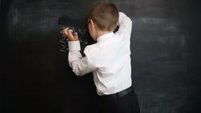 Het jonge bord van de jongenswas na het oplossen van wiskundeuitdrukkingen Creatief concept van terug naar school en studie Presc stock videobeelden