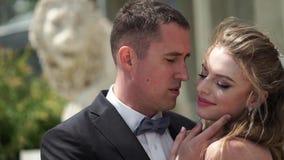 Het jonge bruid en bruidegom stellen in een stad Golvende sluier bij winderige de zomerdag stock footage