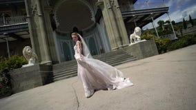 Het jonge bruid stellen in een stad Golvende sluier bij winderige de zomerdag stock footage