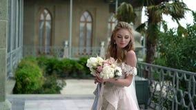 Het jonge bruid stellen in een stad Golvende sluier bij winderige de zomerdag stock videobeelden