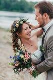 Het jonge bruidegom en bruid bevindende koesteren op de achtergrond van de rivier Stock Fotografie