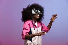 Het jonge bruin-haired krullende meisje van mod. gekleed in de roze blazer gebruikt de virtuele werkelijkheidsglazen in de studio royalty-vrije stock afbeelding
