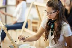 Het jonge bruin-haired meisje in glazen gekleed in witte t-shirt en jeans met een sjaal rond haar hals schildert binnen een beeld royalty-vrije stock fotografie
