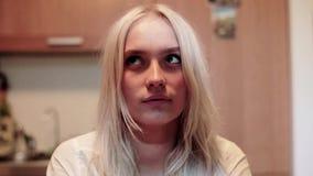 Het jonge bruine eyed leuke glimlachende blonde met nieuwsgierig gezicht staart omhoog bij plafond stock footage
