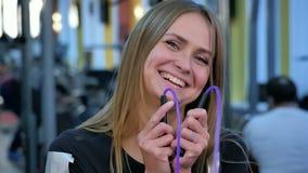 Het jonge camera bekijken en touwtjespringen die van de sportvrouwholding, die glimlachen stock video