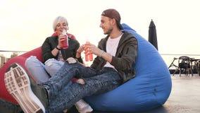 Het jonge charmante hipster paar heeft pret in het zitten op leunstoelzakken met energiedranken op het terras van moderne koffie stock video