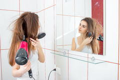 Het jonge charmante meisje bevindt zich voor de spiegelruimte een beetje donkere ingang en droogt haar Stock Fotografie