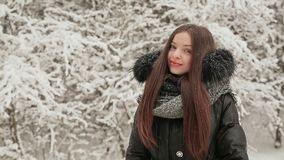 Het jonge charmante meisje kleedde zich in warme de winterkleren die dichtbij snow-covered sparren stellen Glimlachende meisjes g stock videobeelden