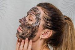 Het jonge charmante meisje maakt een zwart houtskoolmasker op haar gezicht Royalty-vrije Stock Foto