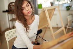 Het jonge charmante meisje met bruin krullend haar gekleed in witte blouse schildert een beeld bij de schildersezel in de tekenin stock foto