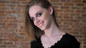 Het jonge charmante meisje met rokerige ogen let op bij camera, het glimlachen, flirtconcept, baksteenachtergrond stock video