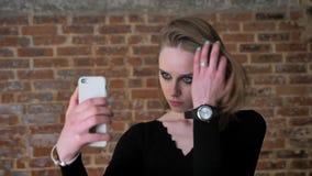 Het jonge charmante meisje met rokerige ogen maakt seifie op haar smartphone, communicatie concept, baksteenachtergrond stock videobeelden