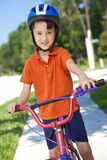 Het jonge Cirkelen van het Kind van de Jongen op Zijn Fiets Stock Fotografie