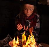 Het jonge dakloze jongen verwarmen door de krantenbrand Royalty-vrije Stock Afbeelding