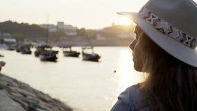 Het jonge dame ontspannen op dijk bij zonsondergang stock footage
