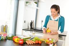 Het jonge de keuken van vrouwen scherpe groenten voorbereidingen treffen Stock Afbeeldingen