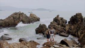 Het jonge de paarmeisje en mens bevinden zich op het strand en houden elkaar de handen van ` s Mooie mening van de oceaan en stock videobeelden