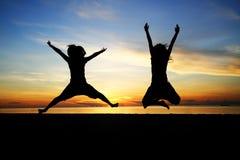 Het jonge de vrouw van het silhouet springen Royalty-vrije Stock Afbeeldingen