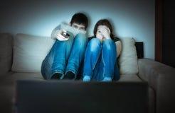 Het jonge doen schrikken paar let op verschrikking op TV Royalty-vrije Stock Foto's