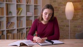 Het jonge donkerbruine langharige vrouwelijke boek van de studentenlezing en het maken van nota's zijnd aandachtig in bureau stock video