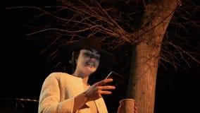 Het jonge donkerbruine meisje bij nacht in een hoed bekijkt de telefoon en drinkt koffie onder de boom stock videobeelden