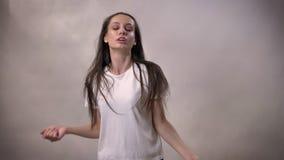Het jonge donkerbruine meisje danst en springt, het glimlachen, bewegingsconcept, grijze achtergrond stock videobeelden